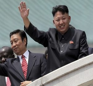 North Korea's leader Kim Jong Un, right, is accompanied by Chinese Vice President Li Yuanchao, center, and Zambia Vice-President Edward Kiwanuka Ssekand as they greet spectators Saturday, July 27, 2013 during the mass military parade celebrating the 60th anniversary of the Korean War armistice in Pyongyang, North Korea. (AP Photo/Wong Maye-E) North Korea Koreas Armistice