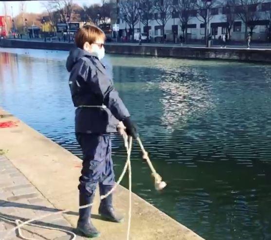 Niño pesca metales con imanes en el rio sena