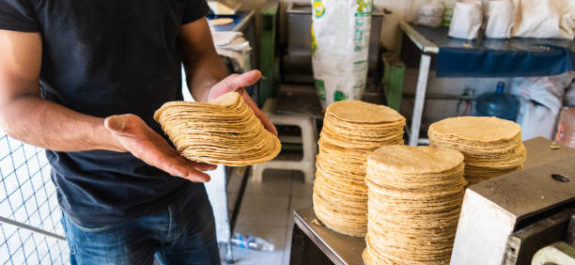 young man selling tortillas of nixtamal in typical mexican shop